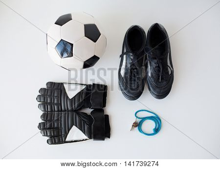 sport,  football and sports equipment concept - close up of soccer ball, whistle, gloves and boots