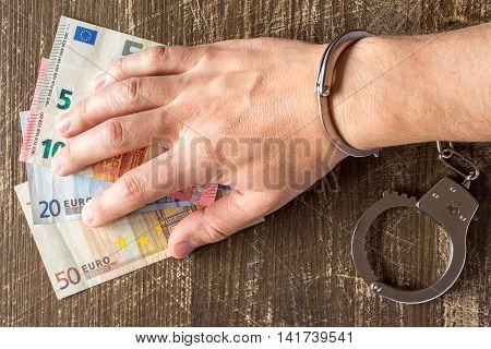 Hand in handcuffs on Euro currency banknotes