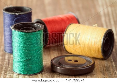 Spools of thread and button on wooden background.