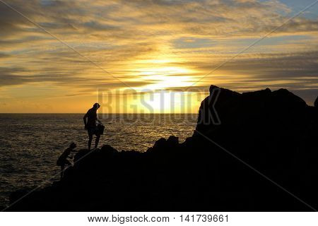Two persons walking on rocks at sunset when they return from fishing.