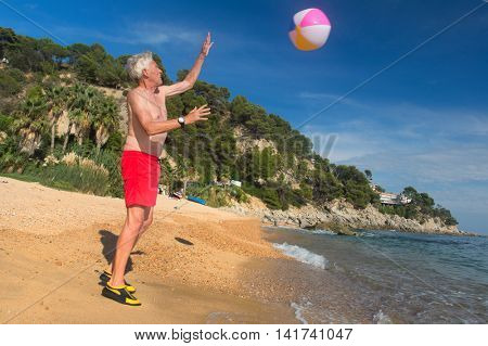 Man playing with inflatable ball at the beach