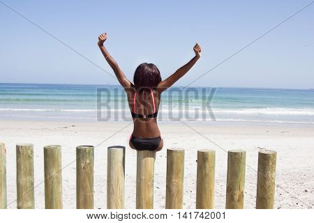 Back-view of a slim african girl in a bikini sitting on a wooden slab and looking out over the ocean with her arms raised