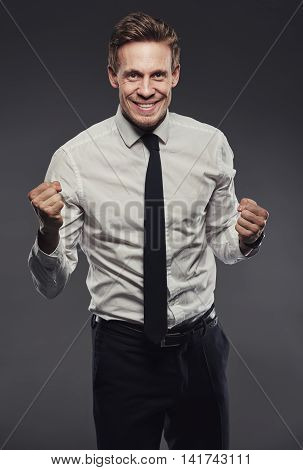 Handsome young businessman in a shirt and tie looking celebrating success standing with against a gray background