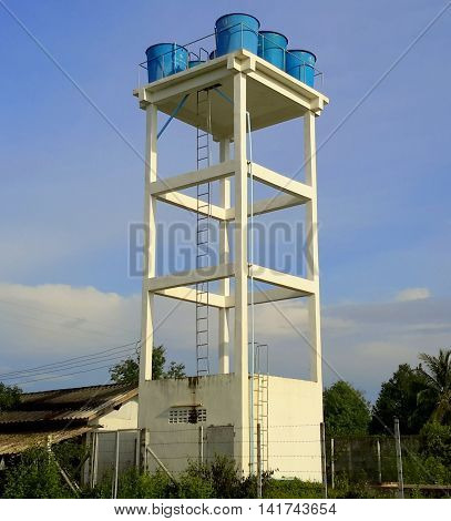 white cinder block four-story water tower with blue plastic water barrels at the top, blue sky and clouds, Songkhla, Thailand