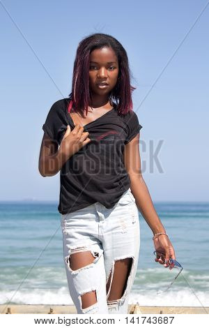 An attractive ethnic woman in casual clothing looking in a seductive manner at the camera with the ocean behind her