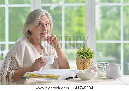 Portrait of a senior woman with book at home