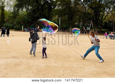 Barcelona Spain - April 4 2016: Children catching the soap bubbles in the in the Ciutadella Park in Barcelona. Ciutadella park is one of the finest parks in Barcelona. Park dotted with historic landmarks statues and fountains