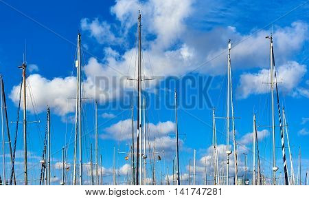 Ship masts against blue cloudy sky. Port of Barcelona Spain
