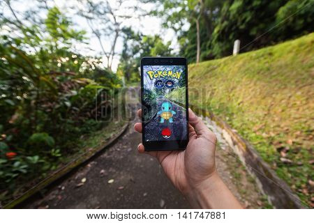 California, United States - July  23, 2016: Close up view of a person hand holding a smartphone and playing Pokémon Go
