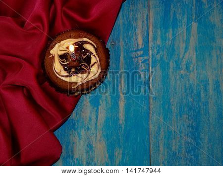 chocolate birthday cake lies on a blue wooden boards and a red silk laid in the crease