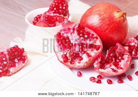 Piece of juicy ripe pomegranate on a white plate closeup
