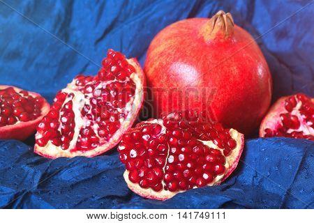 Juicy ripe pomegranates on dark blue background