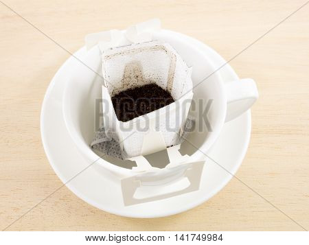 The instant freshly brewed coffee drip bag on white coffee cup.