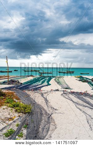 view of large fishing nets on african seashore with ocean and boats on the background