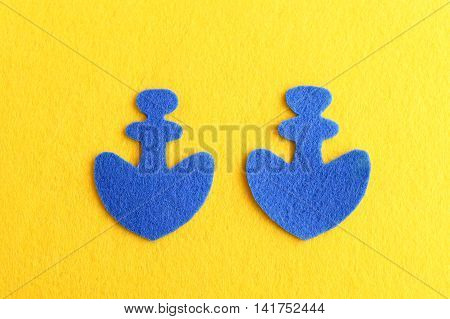 Cut out felt shapes of an anchor. Two blue felt anchor isolated on yellow background. Sewing crafts for children, women, beginners. Step. Top view