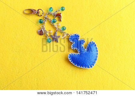 Anchor charm keychain for beach bag. Blue felt anchor keychain with beads isolated on a yellow background. Sewing technique for children, women, beginners. Simple summer crafts. Step. Top view