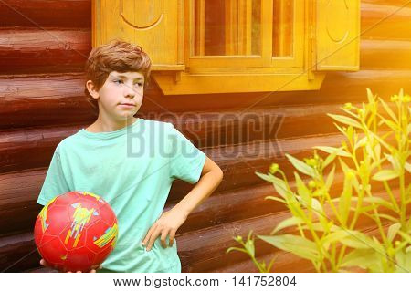 preteen handsome boy with soccer ball close up photo on the country log house background