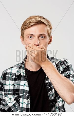 Close up portrait of handsome confident blond young man wearing casual plaid shirt covering mouth with hand looking in camera, isolated on grey background