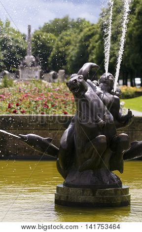 PORT SUNLIGHT, ENGLAND, JUNE 29. A pool and fountain on June 29, 2016, in Port Sunlight, England. A man and boy on a horse flanked by dolphins sprays water into a pool in Port Sunlight England. The War Memorial is in the background.