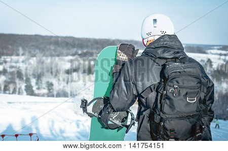 people in ski suit holding snowboards on a snowhill view from back