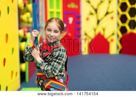 joyful little girl on ropes for climbing in entertainment center