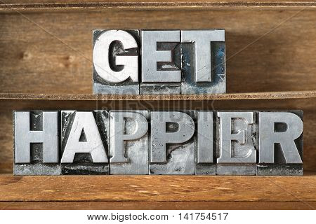 get happier phrase made from metallic letterpress type on wooden tray