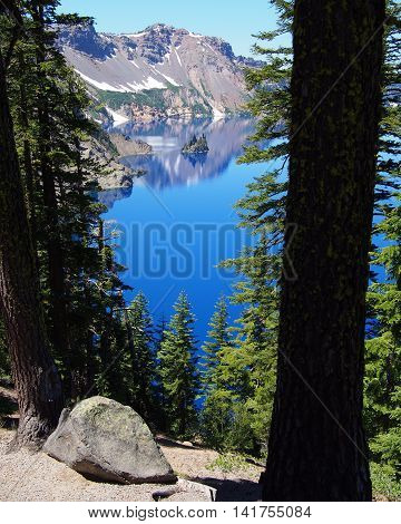 A nice view of Crater Lake's Phantom Ship through the forest as it sits in the reflection of the crater wall.