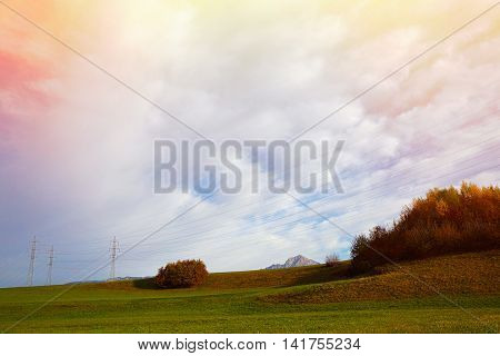 Electrical power distribution lines with pylons on a green pasture in autumn nature against dramatic evening sky and mountains in the background. Power generation distribution and industry concept.