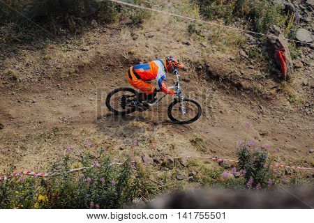 Magnitogorsk Russia - July 23 2016: young rider athlete on bicycle rides on a mountain trail during National championship downhill