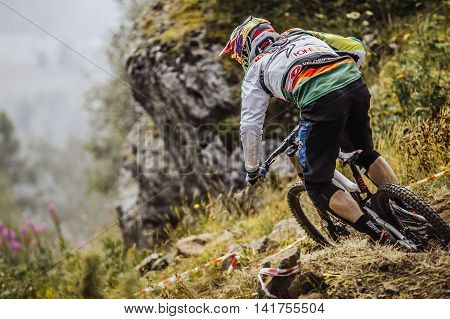 Magnitogorsk Russia - July 23 2016: closeup of a young rider athlete on bike rides on a mountain trail during National championship downhill