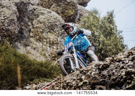 Magnitogorsk Russia - July 23 2016: closeup of a young rider athlete on bicycle on a rock during National championship downhill