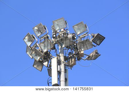 Many bright spotlights on a pole against the blue sky