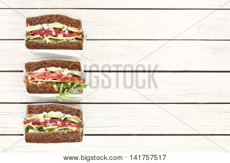 Wrapped delicious salami sandwiches on white background.
