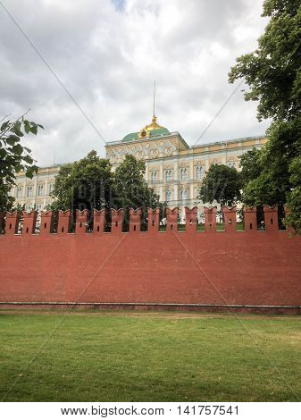 MOSCOW, RUSSIA, JULY 3, 2014: view of red Kremlin wall, green grass, and the Grand Kremlin Palace, mid-afternoon