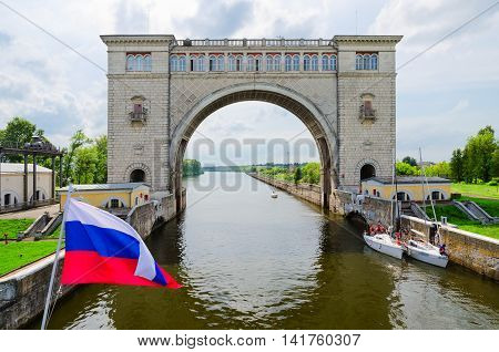 UGLICH RUSSIA - JULY 19 2016: Russian flag on background of arch of navigation lock of Uglich hydroelectric power station. Team of unknown yachtsmen expects decline of water level for passage of gateway