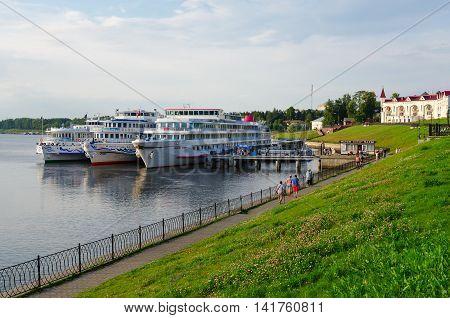 UGLICH RUSSIA - JULY 19 2016: Unidentified people walk along promenade of old Russian town of Uglich. Cruise ship