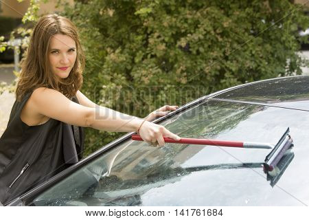 brunette woman cleaning the windshield of her car