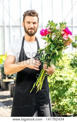 Handsome flower seller making a beautiful bouquet with pink peonies in the flower shop