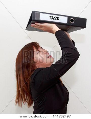 Closeup portrait of stressed or unhappy businesswoman shoulder heavy task folder hard work business concept.