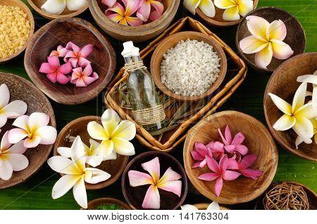 wooden bowl of color sea salt with , ,massage oil and frangipani, on banana leaf