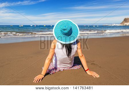Woman in hat enjoying sun holidays on the beach of Gran Canaria