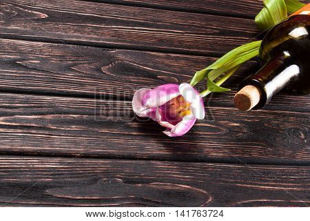 Tulip and wine on wood background. Nature background