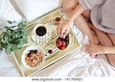 Healthy Breakfast in Bed, girl eating breakfast, top view