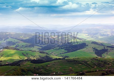 landscape consisting of a Carpathians mountains with fir-trees and green grassy valley and cloudy skies on the background