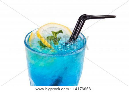 blue alcoholic cocktail in transparent glass with lemon and mint