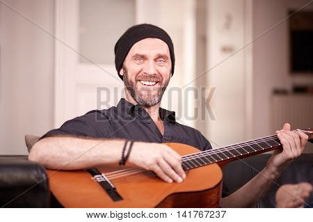 Hipster Playing Guitar And Smiling To Camera