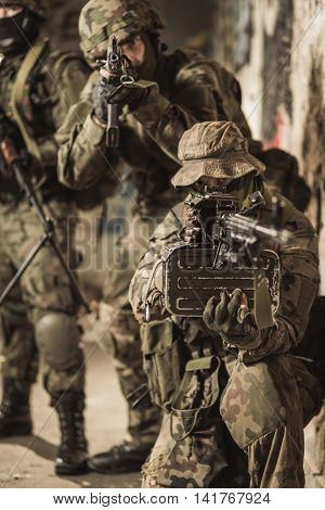 Shot of three soldiers with the one kneeling pointing by the weapon