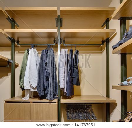 Wardrobe with wooden shelves and drawers. On crossbars hang clothes and hangers, on shelves stand shoes.