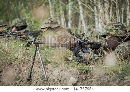 Soldiers laying on a training ground with the weapon with the forest behind them
