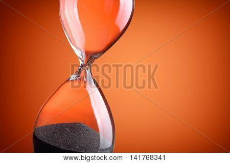 Closeup  photo of hourglass on orange background
